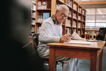 Senior man writing sitting in a university classroom