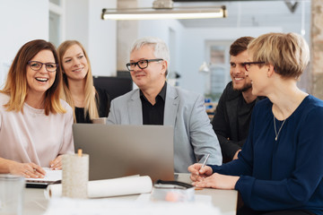 Happy business team laughing during a meeting