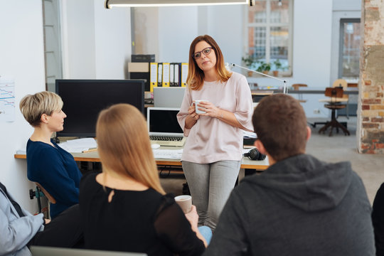 Woman in office talking to her colleagues