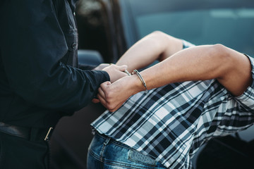 Police officer puts handcuffs on a car thief