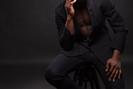 Beautiful and muscular black man in dark background.