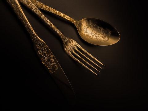 Luxury gold silverware set with soft lighting