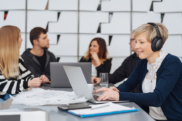 Woman working in office in wireless headphones