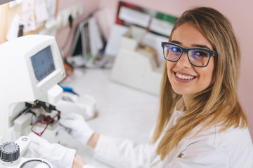woman ophthalmologist working in optics store