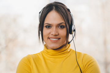online customer support.portrait of woman with microphone and headphones looking at camera