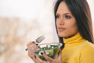 portrait of young woman holding healthy fresh salad
