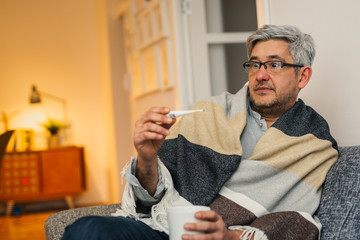 sick middle aged man sitting sofa and looking at thermometer