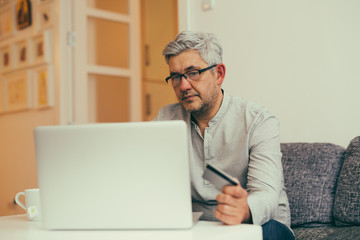 middle aged man using laptop for online shopping from his apartment