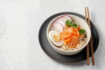 Bowl of veggie noodle broth ramen with egg, carrot, radish and sesam