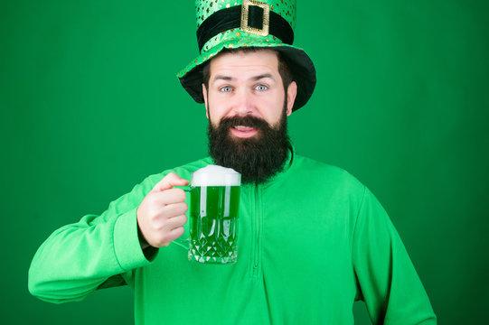 St Pats green giveaway. Irish man with beard drinking green beer. Celebrating saint patricks day in bar. Bearded man toasting to saint patricks day. Hipster in leprechaun hat holding beer mug