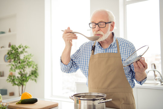 Close up photo grey haired he his him grandpa appetite waiting guests cooking favorite family dish trying taste wait ready wear specs casual checkered plaid shirt jeans denim outfit kitchen indoors