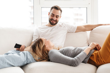 Amazing loving couple sitting indoors at home watch TV holding remote control.