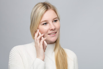 young blonde woman is talking on the mobile phone