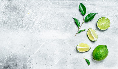 Pieces of fresh juicy lime with foliage. Wall mural