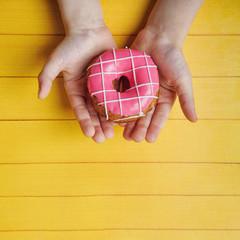 Little kids hands holding  sweet donut dessert.