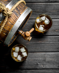 Whiskey in glasses with ice and a wooden barrel.