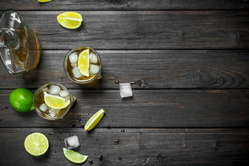 Whiskey in glasses and a bottle of lime slices.