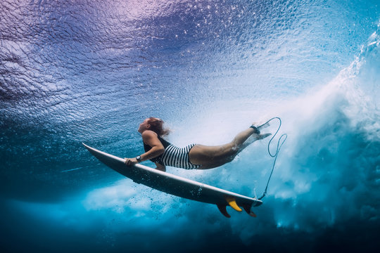 Surfer woman dive underwater. Surfgirl dive under big wave