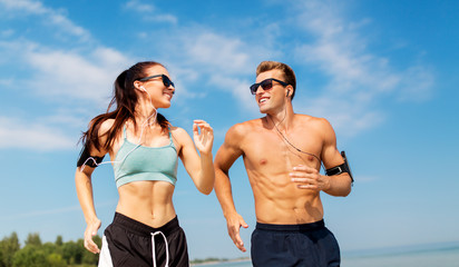 fitness, sport and technology concept - happy couple with earphones and arm bands running along summer beach