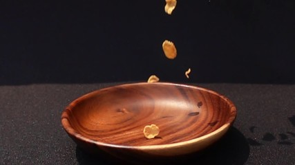 Fototapete - Crispy yellow corn flakes fall into a wooden bowl on black background in Slow Motion