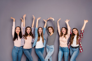 Close up photo yelling glad beautiful she her six ladies skinny roommates hands arms raised up delighted wearing casual jeans denim checkered striped clothes outfit isolated grey background