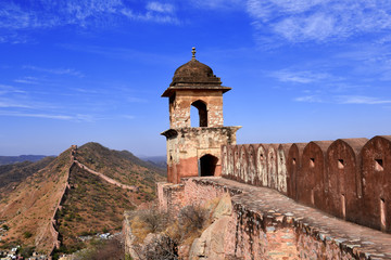 Fototapete - ancient watchtower in the great indian wall overlooking the city of Amer near to the Amber Fort, Radjasthan, Jaipur, India