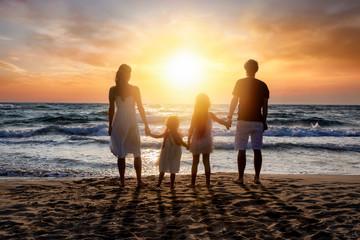 Glückliche Familie im Sommerurlaub steht händehaltend am Strand und genießt den Sonnenuntergang