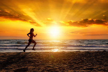 Silhouette einer laufenden Frau bei Sonnenuntergang am Strand während ihres Trainings