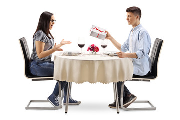 Young male giving a present to a young female at a restaurant table