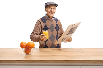 Elderly man holding a glass of orange juice and a newspaper behind a wooden counter