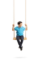 Boy sitting on a swing and looking away