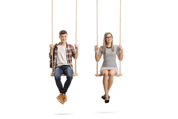 Teenage male student and a young woman sitting on a swing