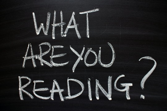 The question What Are You Reading written by hand in white chalk on a blackboard