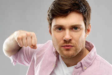 violence, aggression and people concept - angry young man ready for fists punch over grey background
