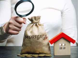 A female hand is holding a magnifying glass over a money bag with the word Mortgage and a wooden house. Concept analysis of mortgage lending rates and interest in the mortgage. Real estate market