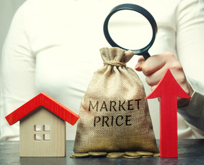 A female hand is holding a magnifying glass over a money bag with the word Market price, up arrow and a house. The concept of increasing housing prices. Rising rent. Real estate market growth
