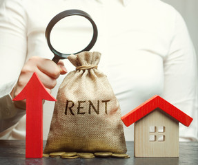 A female hand is holding a magnifying glass over a money bag with the word Rent, up arrow and a house. The concept of raising the rent for an apartment or home. Growing demand for rental housing