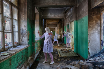 three identical nurses without faces (head bandaged) zombies with a knife and syringe in an abandoned hospital or an insane asylum. Maybe picture for horror movie
