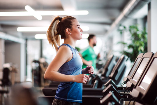 A portrait of young girl or woman doing cardio workout in a gym.