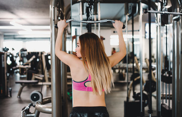 A rear view of young girl or woman doing strength workout in a gym.