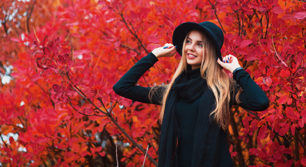 Fashion autumn portrait smiling woman in black hat on a red leaves background