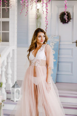 Sexy girl in pink negligee poses in a spring studio
