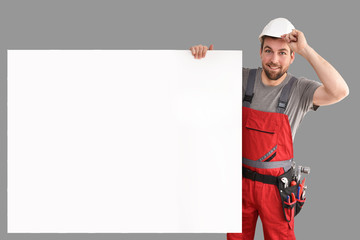 friendly craftsman points to a free billboard - isolated worker with work clothes