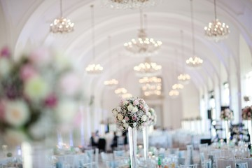 Big wedding hall well decorated in pastel colors - chandeliers on vaulting.