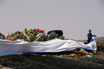 An Ethiopian man covers the debris of the Ethiopian Airlines Flight ET 302 plane crash before a commemoration ceremony at the scene of the crash, near the town of Bishoftu, southeast of Addis Ababa