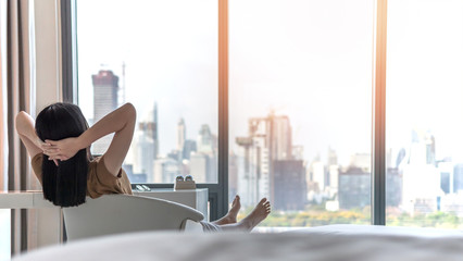Life quality concept with young woman relaxing and resting in comfortbusiness hotel guest room or luxury home living room looking toward beautiful city view of cityscape