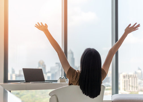 Life balance and summer holiday vacation concept with happy young woman taking a break, celebrating successful work done, casually resting in luxury city hotel workplace with computer laptop on desk