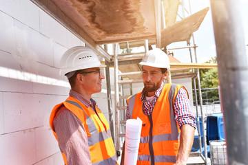 Architekt und Bauleiter auf der Baustelle beim Hausbau // construction manager and architect on site during the construction of a house - planning and control on site - teamwork