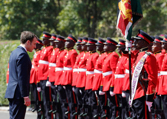 French President Emmanuel Macron inspects a guard of honour by the Kenya Defence Forces at State House in Nairobi