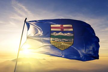 Alberta province of Canada flag waving on the top sunrise mist fog